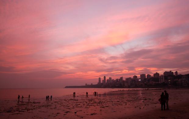 Люди стоят на побережье Аравийского моря после заката в Мумбаи 1 ноября 2012 года. Rajesh Kumar Singh