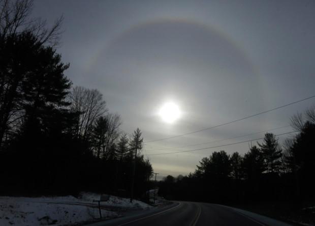 Атмосферное явление, известное как солнечная собака (или паргелий) появляется на небе. Форт-Энн, Нью-Йорк, 25 января 2013 года. Гало вокруг солнца вызвано преломлением солнечного света о мелкие кристаллы льда в атмосфере. Gary Hershorn