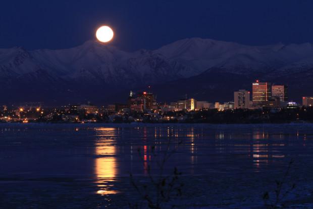 Полная луна поднимается над горами Chugach, Анкоридж, штат Аляска, и отражается в водах залива Кука. 26 января 2012 года. Dan Joling