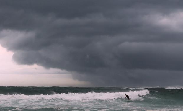 Серфер ждёт большую волну, пока сгущаются тучи над пляжем после ветров и сильных дождей. Сидней, 29 января 2013 года. Mark Metcalfe