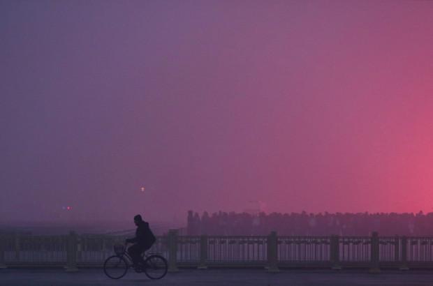 Велосипедист едет у перил моста на площади Тяньаньмэнь. Над городом висит смог 29 января 2013 года. Пекине. Feng Li