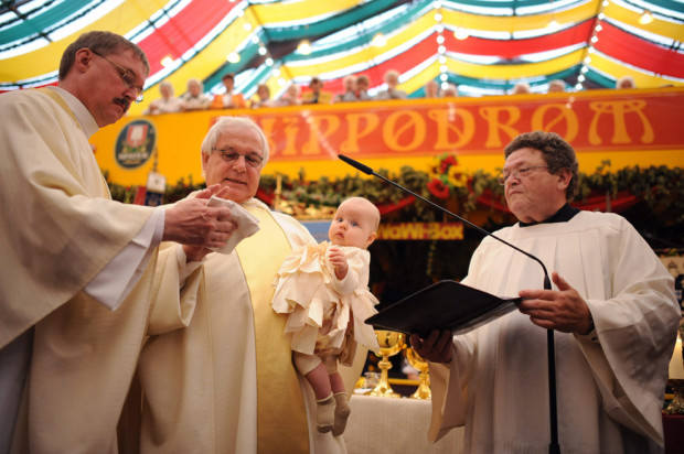 Отец Пауль, местный католический священник, крестит шестимесячную Элизу. Да, всё это происходит на пивном фестивале!