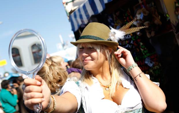 Софья Трайгер примеряет шляпу. Десять лет назад официантки на Октоберфесте были единственными, кто одевался в традиционный баварский крестьянский костюм: корсет, платье, белая блузка, цветной фартук. Теперь, ежегодный фестиваль Октоберфест в Мюнхене - это море туристов в традиционных костюмах, причём в том числе из таких отдаленных стран , как Канада, Мексика и Иран. Мужчины тоже носят традиционные одежды - ледерхозе (кожаные штаны) и клетчатые рубашки.