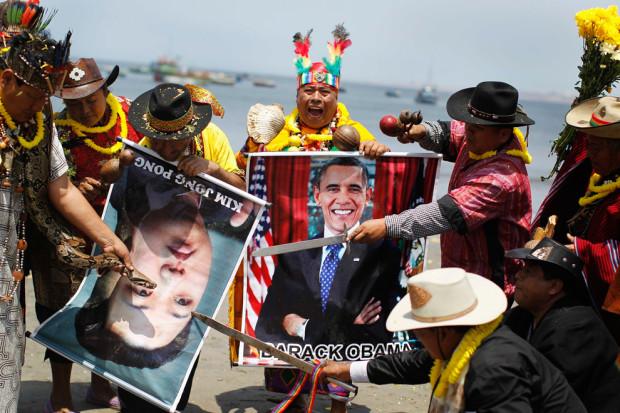 Шаманы держат плакаты с президентом США Бараком Обамой и лидером Северной Кореи по имени Ким Йонг Ун на пляже Agua Dulce , Лима. Старый ритуал, на котором задают вопросы. (Enrique Castro-Mendivil/Reuters)