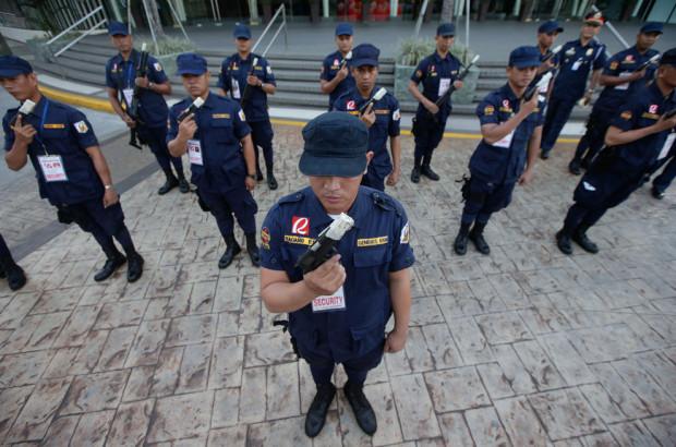 Частная охрана осматривает свои пистолеты после того, как полицеские провели проверку, чтобы владельцы оружия не стали палить из него на Новый Год. Традиционно филиппинцы на Новый Год взрывают петарды и вообще очень старательно шумят, а беспорядочная пальба из оружия нередко приводит к жертвам. (Bullit Marquez/AP)