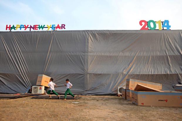 Мальчишки в школьной форме играют рядом с площадкой, где будет проходить празднование. Празднование нового года с публичным обратным отсчётом  в Янгоне, Мьянма. Это лишь второй официальный Новый год, который отмечают в стране публично.  (LYNN BO BO/EPA)
