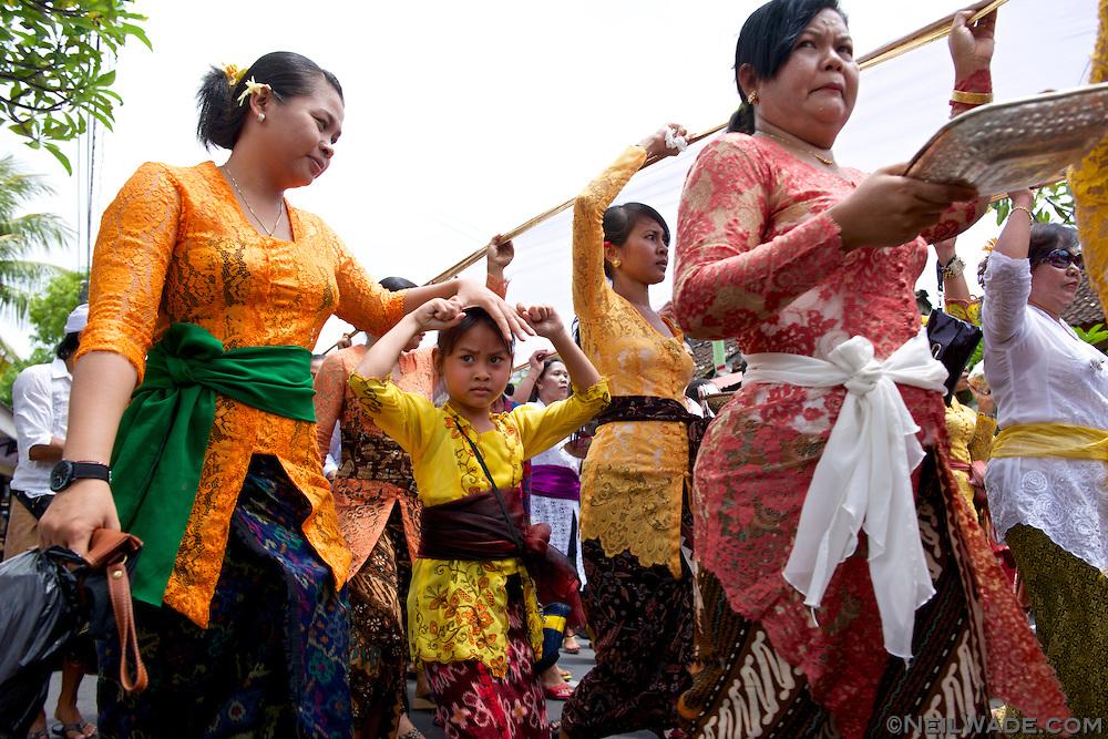 Women walk in a religious Hindu parade in Ubud, Indonesia.