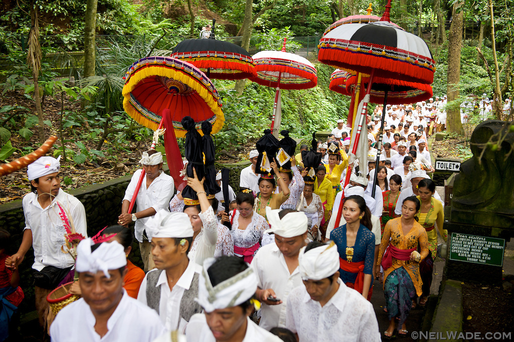 Many people walk in a Hindu parade in Ubud, Indonesia.