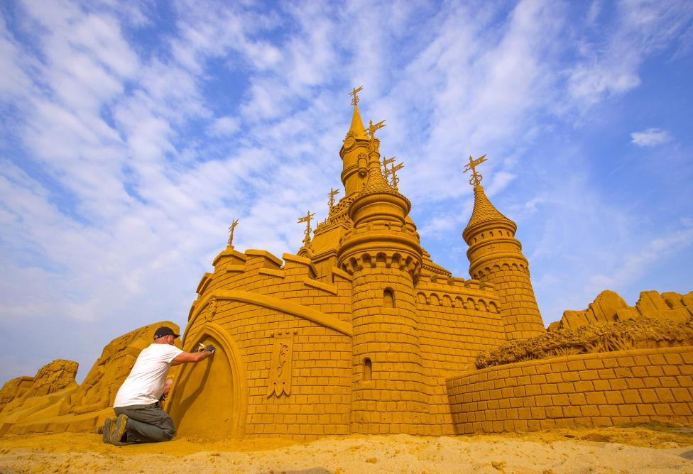 A sand carver works on a sculpture during the Sand Sculpture Festival Frozen Summer Fun in Ostend