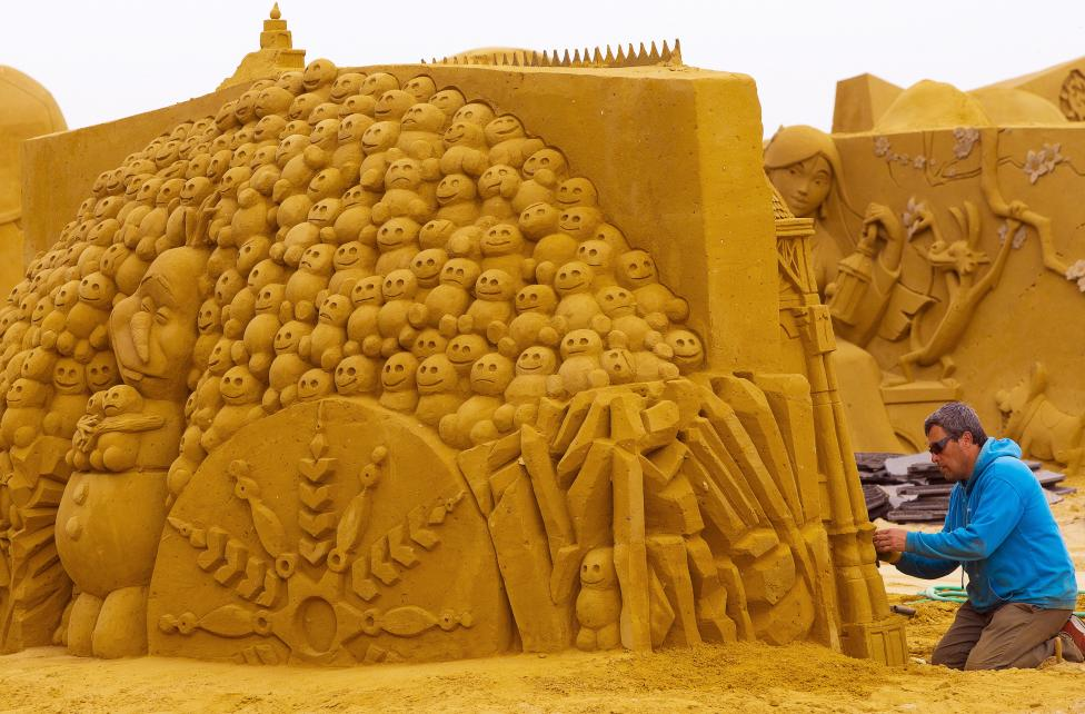 Sand carver Gaspari from Italy works on a sculpture during the Sand Sculpture Festival Frozen Summer Fun in Ostend