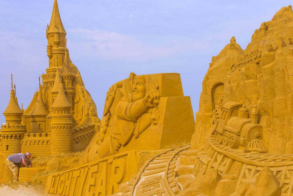 A sand carver works on sculpture during Sand Sculpture Festival Frozen Summer Fun in Ostend