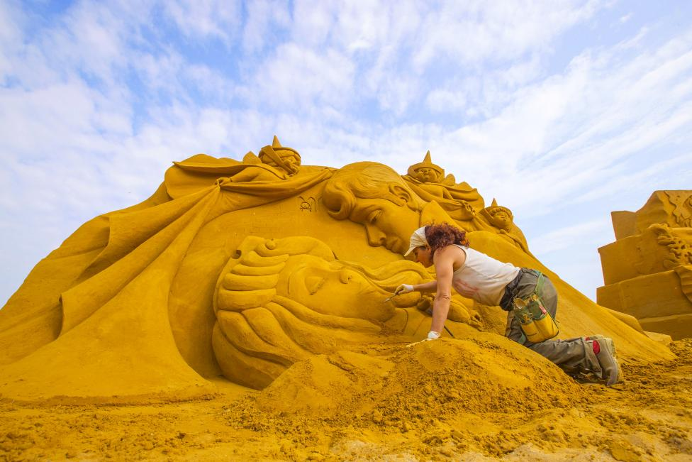 Sand carver Scavuzzo works on a sculpture during the Sand Sculpture Festival Frozen Summer Fun in Ostend