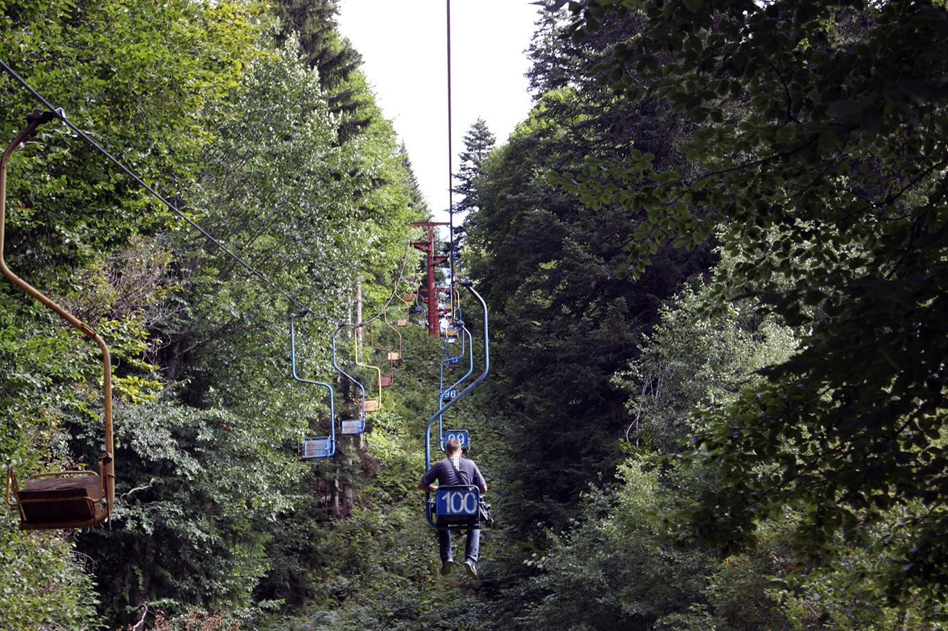 Кресельная канатная дорога идет по лесу
