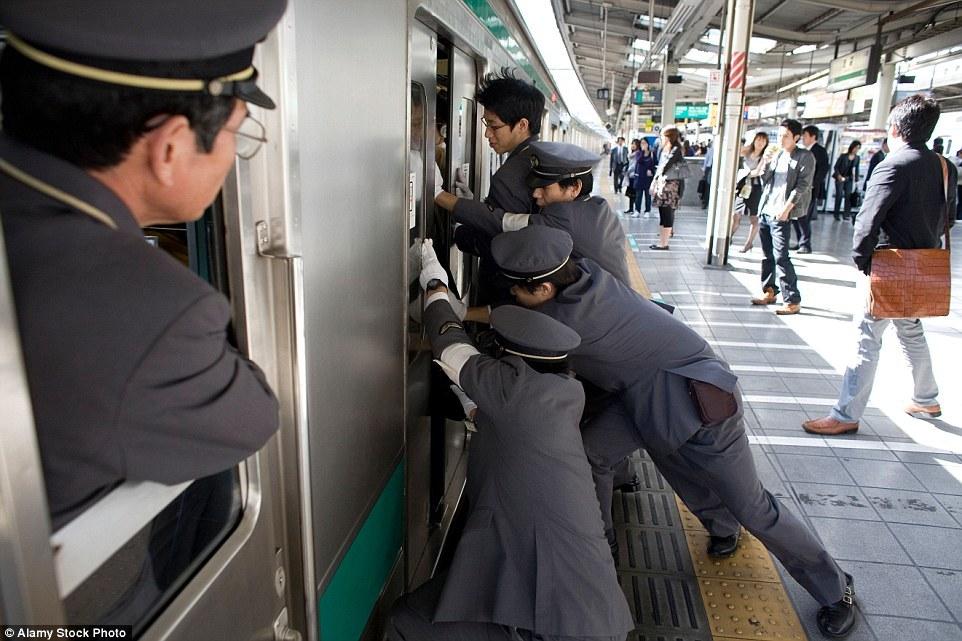 Их задача - затолкать людей в переполненные вагоны