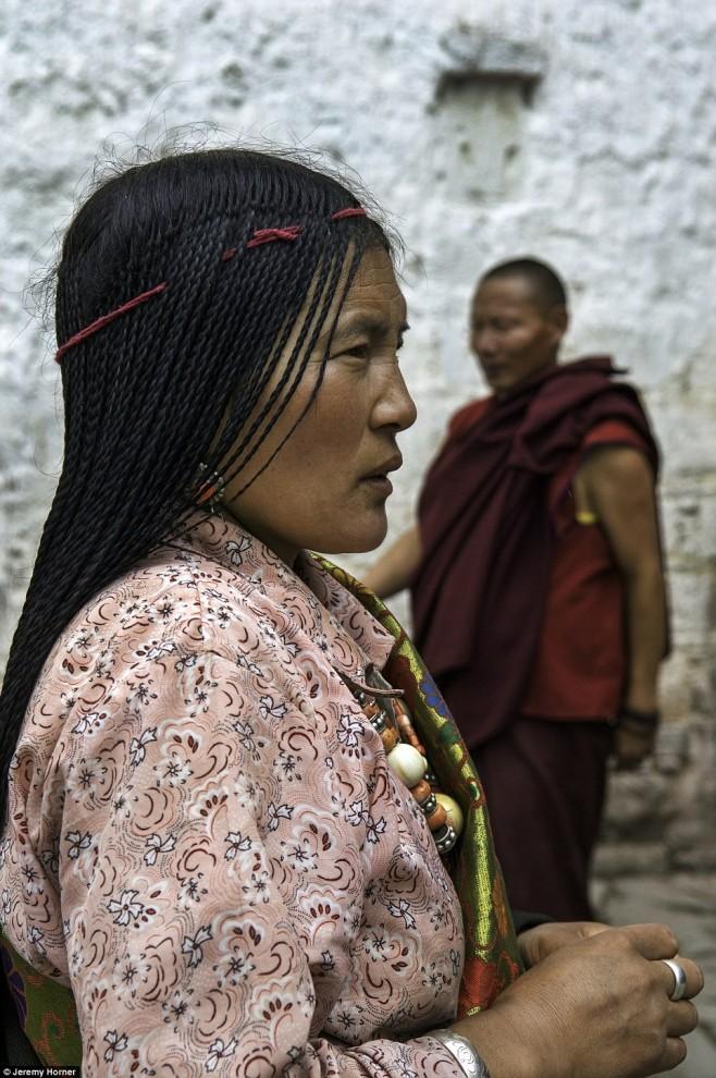 Храм Джоканг – святейшее место в тибетском буддизме. Храм привлекает тысячи паломников. Женщина на фото – одна из них.