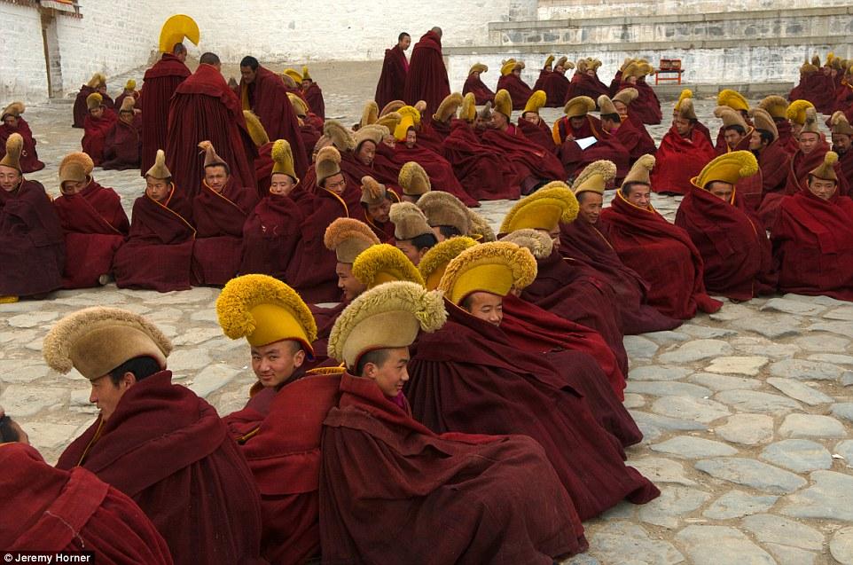 Монахи из школы буддизма Гелугпа в традиционных головных уборах возле монастыря Лабранг в Тибете.