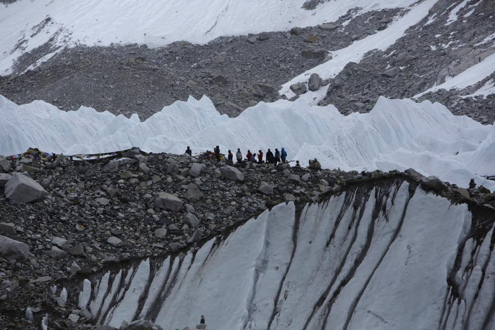 Trekkers stand in Everest Base camp, approximately 5,300 meters above sea level, in Solukhumbu District