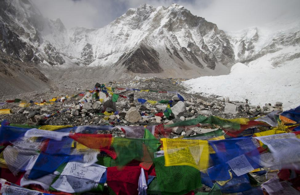 Buddhist prayer flags flutter in the wind with Everest base camp seen in the background