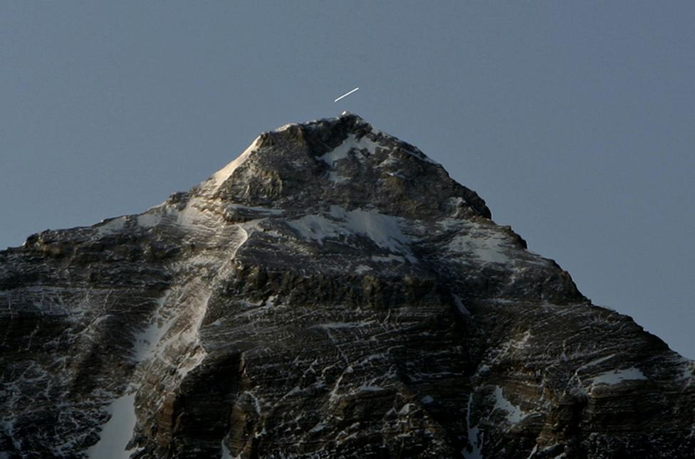 A time exposure shows a star leaving a trail over the summit of the world's highest mountain Mount Everest, also known as Qomolangma, at sunrise in the Tibet Autonomous Region