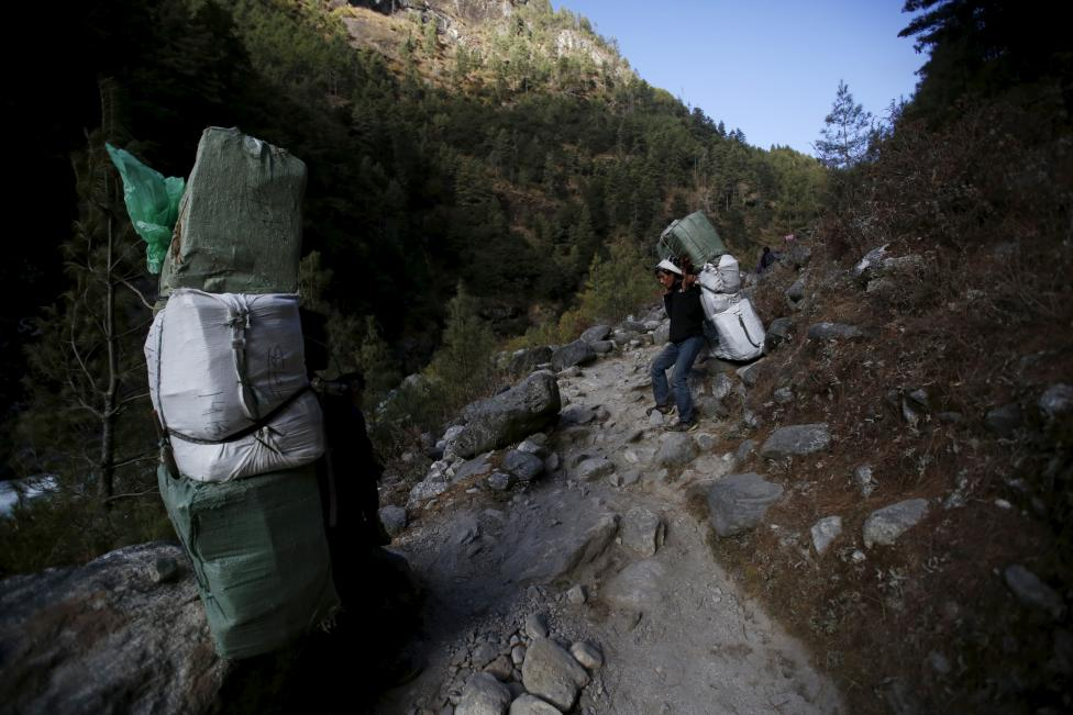 Porters take a break from carrying goods as they head towards Namche in Solukhumbu district, also known as the Everest region